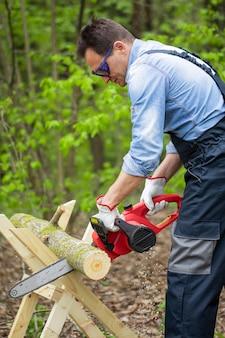 Boscaiolo in uniforme da lavoro sega tronco d'albero sul cavalletto con motosega