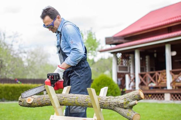 Boscaiolo in uniforme da lavoro sega tronco d'albero sul cavalletto con sega elettrica