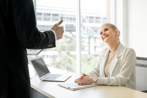 Boss businessman che fa i pollici aumenta la congratulazione all'impiegato di donna allo scrittorio nella stanza dell'ufficio