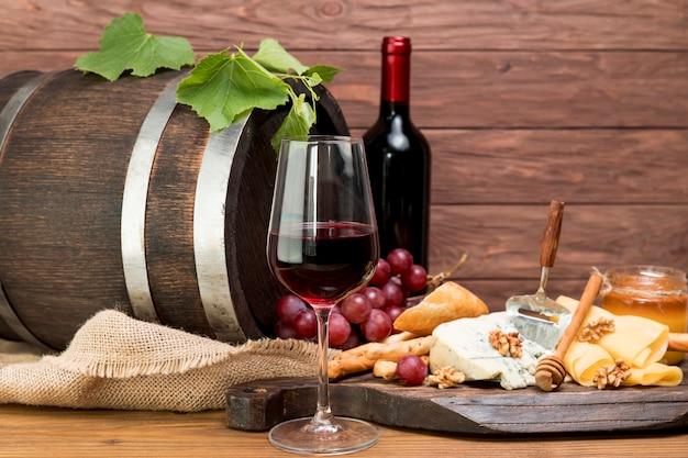 Botte di legno accanto a vino e tapa