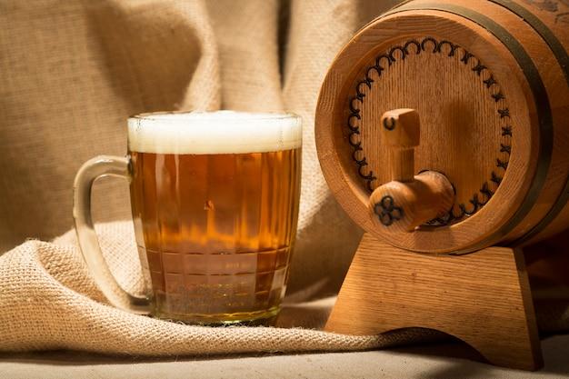 Botte in legno con boccale di birra su tela