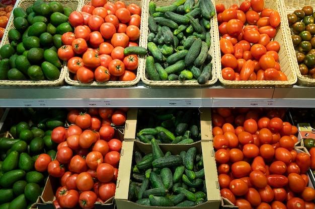 Bottega del supermercato con cestini di vimini e scatole di cartone con pomodori, cetrioli e avocado