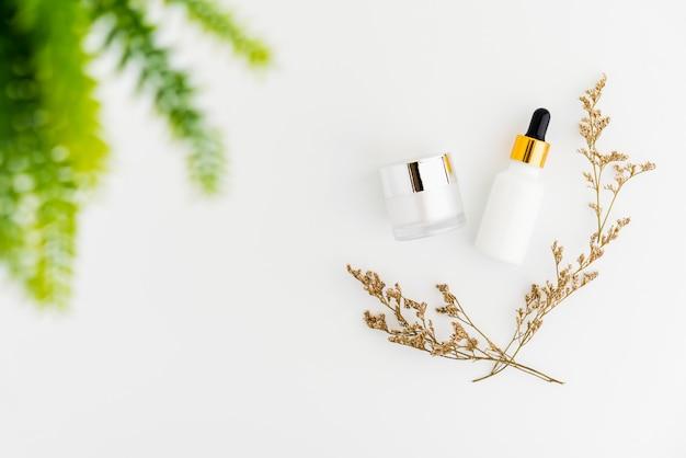 Bottiglia bianca di siero e barattolo di crema, modello del marchio di prodotti di bellezza. vista dall'alto su sfondo bianco.