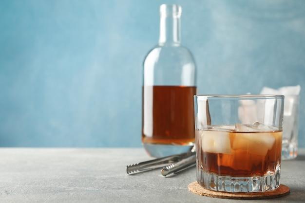 Bottiglia, bicchieri con cubetti di ghiaccio e whisky su sfondo grigio, spazio per il testo
