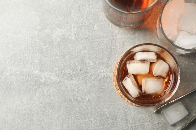 Bottiglia, bicchieri con cubetti di ghiaccio e whisky su sfondo grigio, vista dall'alto