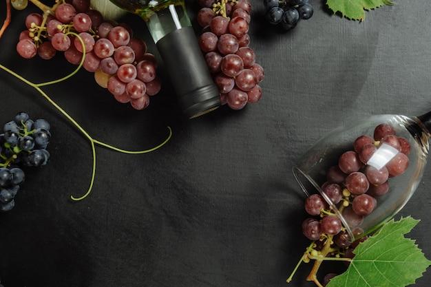 Bottiglia, bicchieri da vino, uva e foglie fresche