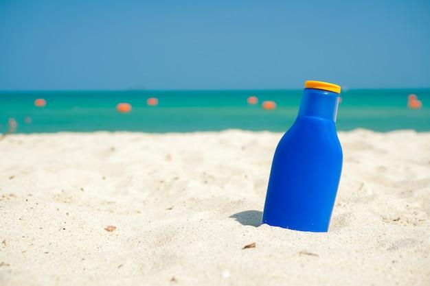 Bottiglia blu del blocco del sole sulla sabbia della spiaggia