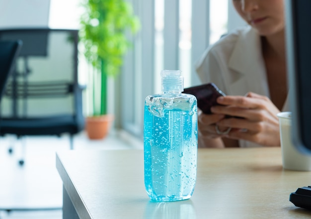 Bottiglia blu del gel dell'alcool per uso nel lavaggio a disposizione disposto sul computer portatile