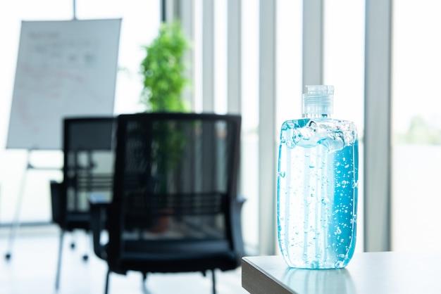 Bottiglia blu del gel dell'alcool per uso nel lavaggio a disposizione disposto sulla tavola in ufficio