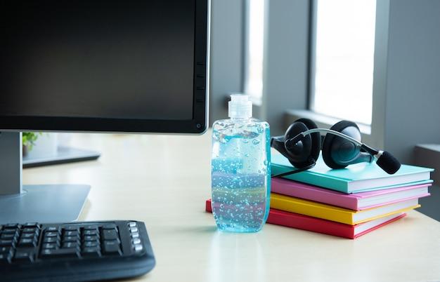 Bottiglia blu del gel dell'alcool per uso nel lavaggio disponibile disposto sulla tavola in posto di lavoro con la cuffia