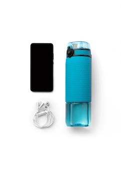 Bottiglia blu piana di vista superiore di disposizione di acqua, delle cuffie e dello smartphone isolata su fondo bianco