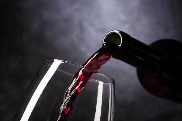Bottiglia che versa vino rosso in vetro