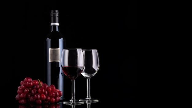 Bottiglia chiusa del vino rosso con etichetta vuota, uva e due bicchieri su sfondo nero con riflessi e copia spazio