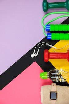 Bottiglia con acqua, orologio intelligente, auricolari e corda per saltare.