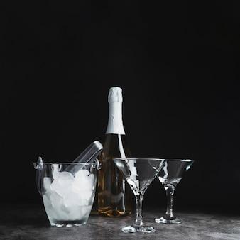 Bottiglia con bicchieri di champagne e ghiaccio