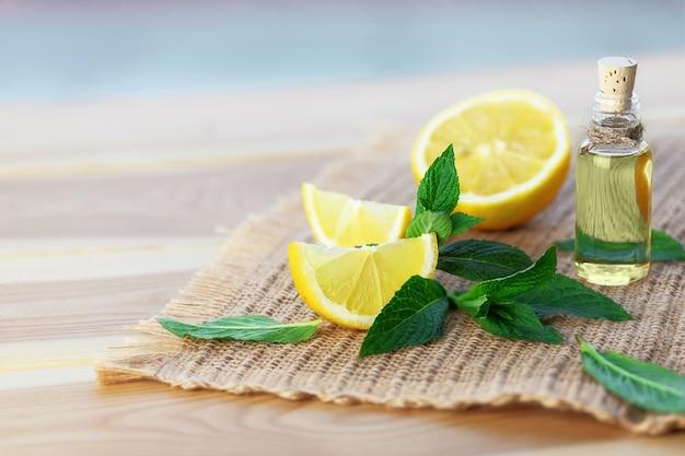 Bottiglia con olio di menta, limone e foglie di menta verde fresca su fondo di legno. messa a fuoco selettiva.