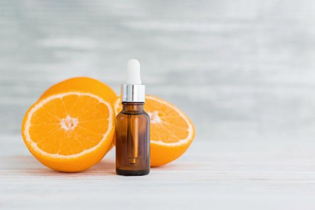 Bottiglia con olio essenziale di arancia naturale di agrumi su legno