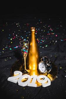 Bottiglia con orologio e cifre 2019 sul vassoio