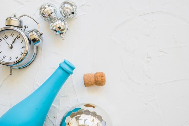 Bottiglia con orologio e gingilli sul tavolo bianco