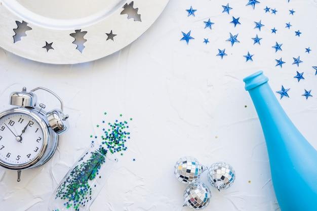 Bottiglia con orologio e lustrini sul tavolo