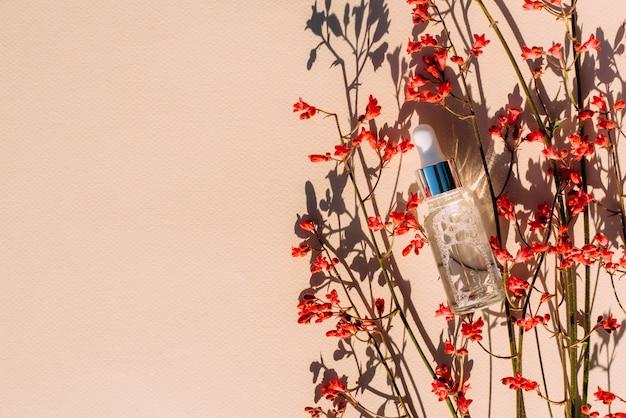 Bottiglia cosmetica con fiori di siero rosso