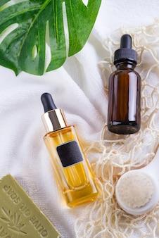 Bottiglia cosmetica con siero e acido ialuronico, foglia di palma, sapone alle olive e borse della spesa riutilizzabili su un asciugamano bianco