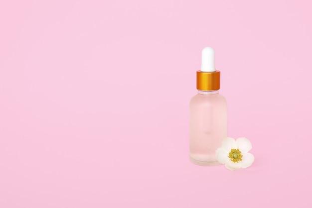 Bottiglia cosmetica in vetro con olio. contenitore per un prodotto per donna con piccoli fiori bianchi su una parete turchese. barattolo cosmetico. posto per il testo