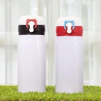 Bottiglia d'acciaio su fondali di tende. contenitore per bevande isolato.