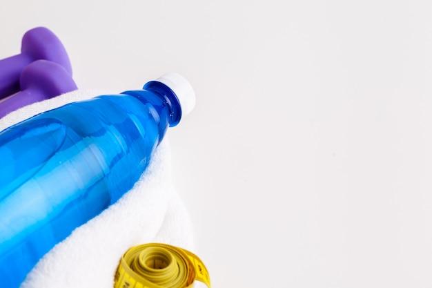 Bottiglia d'acqua e attrezzatura per il fitness isolata