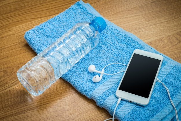 Bottiglia d'acqua in plastica, auricolari, smartphone e asciugamano sul tavolo di legno