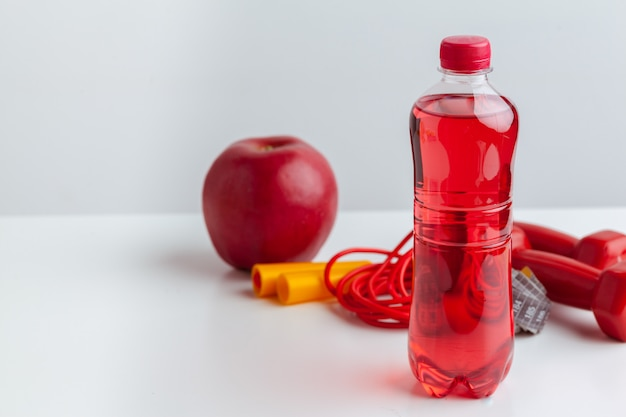 Bottiglia d'acqua, nastro di misurazione e mela fresca sul tavolo
