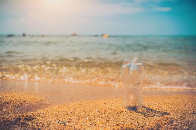 Bottiglia d'acqua o immondizia sulla spiaggia del mare con lo sfondo del mare e la luce del sole