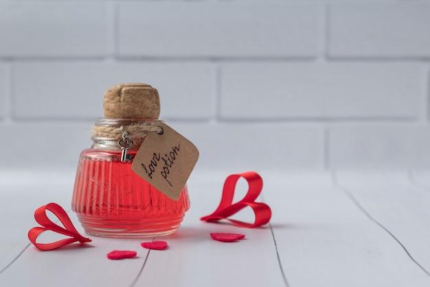 Bottiglia d'annata con pozione d'amore magica sulla tavola di legno bianca, spazio per testo