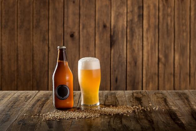Bottiglia da birra e vetro su fondo di legno