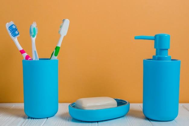 Bottiglia degli erogatori del sapone e del sapone degli spazzolini sullo scrittorio bianco contro la parete