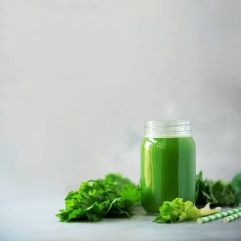 Bottiglia del frullato verde del sedano su fondo concreto grigio con lo spazio della copia