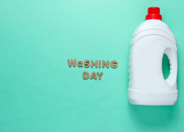Bottiglia del gel di lavaggio su superficie blu con il giorno di lavaggio del testo
