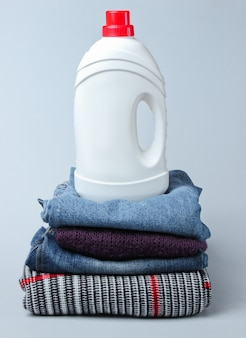 Bottiglia del gel di lavaggio sulla pila di vestiti sulla tavola grigia.