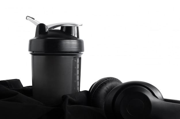 Bottiglia dell'agitatore della proteina del siero di latte con la cuffia su abiti sportivi neri isolati su bianco
