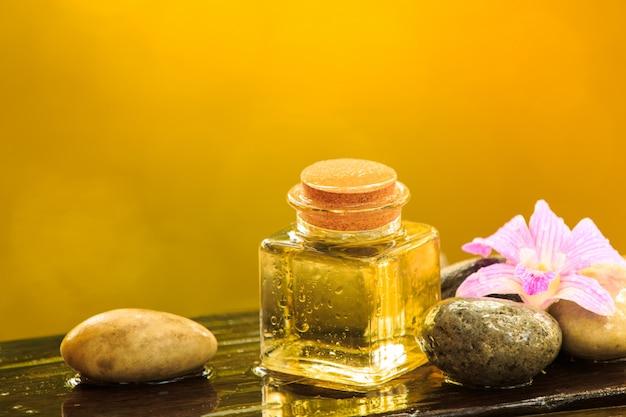 Bottiglia dell'olio essenziale o della stazione termale dell'aroma con la pietra di zen sulla tavola di legno, immagine per il concetto dell'aroma della medicina di terapia alternativa dell'aroma della stazione termale dell'aroma e