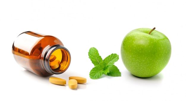 Bottiglia della medicina della mela e della menta di pillola di vetro marroni isolate su bianco