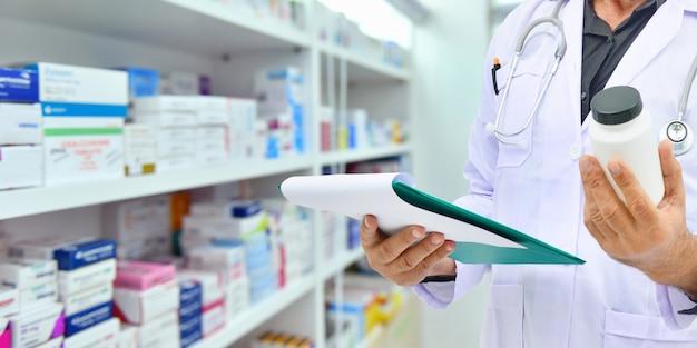 Bottiglia della medicina della tenuta del farmacista e compressa del computer per il riempimento della prescrizione nella farmacia della farmacia