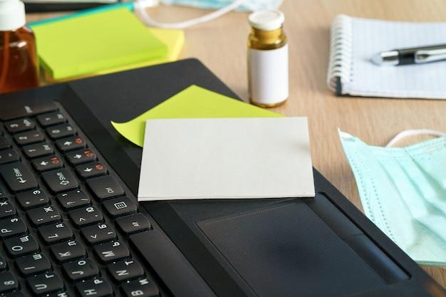 Bottiglia della medicina su una tabella dell'ufficio con la fine del computer portatile in su