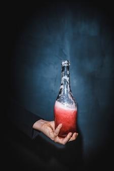Bottiglia della tenuta della mano con bevanda rossa