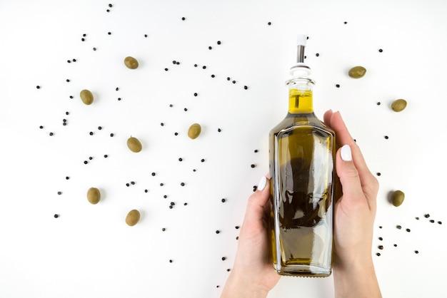 Bottiglia della tenuta della mano del primo piano di olio d'oliva