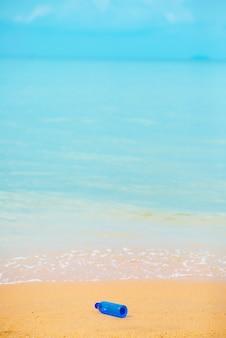 Bottiglia di acqua blu sulla spiaggia con lo sfondo del mare blu