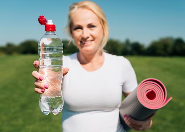 Bottiglia di acqua confusa della tenuta della donna di vista frontale
