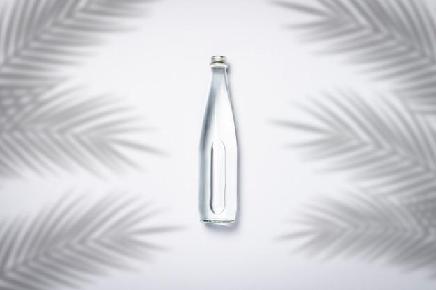 Bottiglia di acqua cristallina pura su uno sfondo bianco sotto le foglie di palma e la luce del sole. banner. concetto di sete, caldo, estate, tropico. vista piana, vista dall'alto
