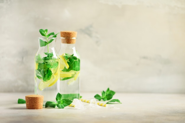 Bottiglia di acqua detox con menta, limone su sfondo grigio. limonata di agrumi la frutta estiva ha infuso acqua.