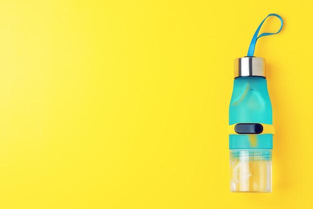 Bottiglia di acqua di limone su sfondo giallo